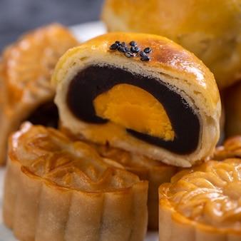 Lekker gebakken eierdooier gebak maan cake voor mid-autumn festival op zwarte leisteen donkere achtergrond. chinees feestelijk voedselconcept, close-up, kopieer ruimte.