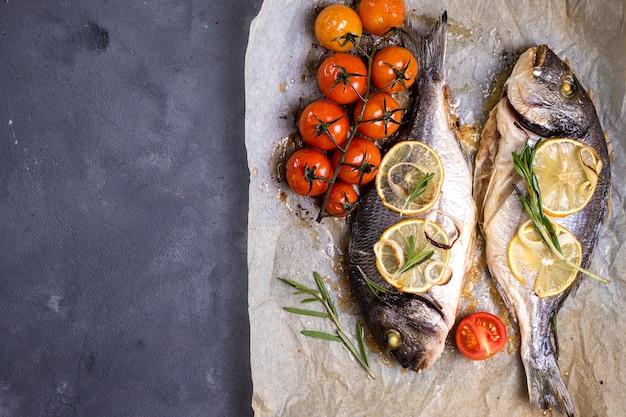 Lekker gebakken hele vis op bakpapier. gebakken zeebrasem met citroen, ui, kruiden, kerstomaatjes, kruiden op donkere rustieke achtergrond. gegrilde heerlijke vis.