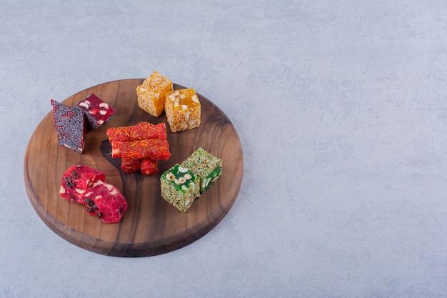 Lekker gedroogd fruitpulp met noten op een houten bord.
