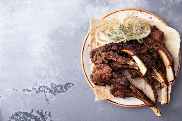 Lekker gegrild lamsvlees op een bord. . bovenaanzicht