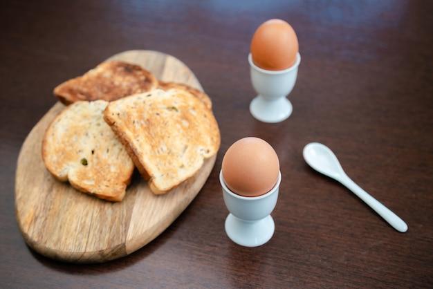 Lekker gekookt ei in een kopje met knapperig geroosterd brood als ontbijt.