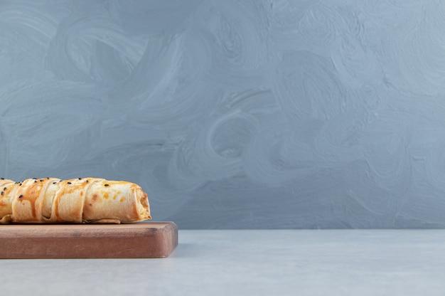 Lekker gevlochten broodje op een houten bord.