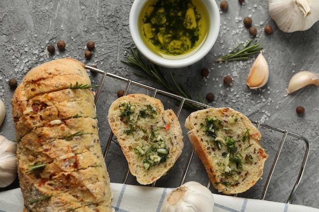 Lekker knoflookbrood en specerijen op grijze, bovenaanzicht