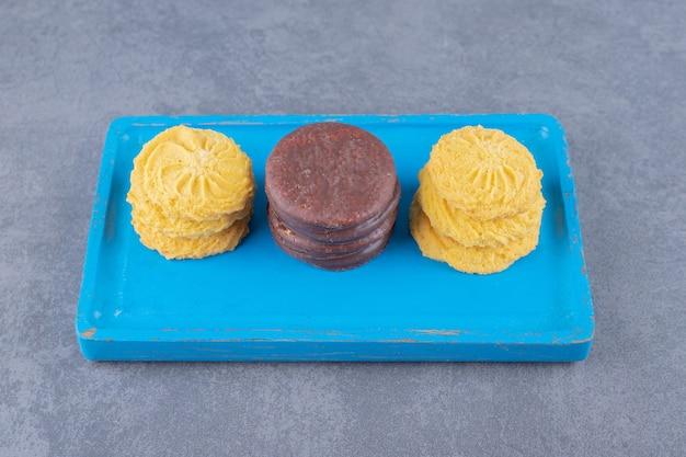 Lekker koekje op een houten bord op marmeren tafel.