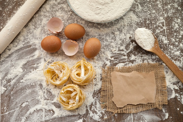 Lekker koken met kippeneieren, bloem en fettuccine. uitzicht van boven.