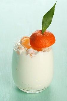 Lekker melkdessert met verse mandarijnstukjes in glas, op een houten kleurentafel