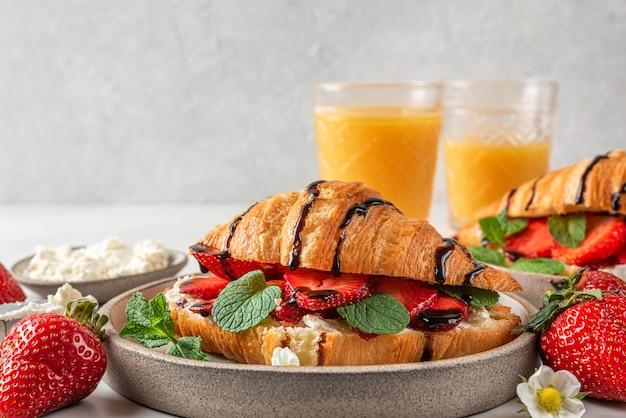 Lekker ontbijt. croissants met verse aardbeien, roomkaas, munt en chocoladesaus met sinaasappelsap Premium Foto