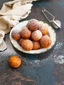 Lekker ontbijt. de ballen van kwarkdonuts met suikerpoeder op een donkere achtergrond. detailopname. kopieer ruimte,