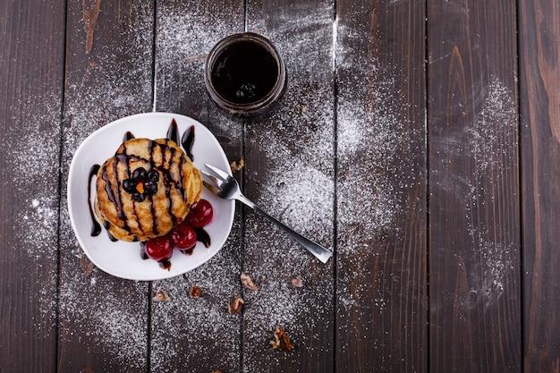 Lekker ontbijt. heerlijke pannekoeken bedekt met chocolade en kersen
