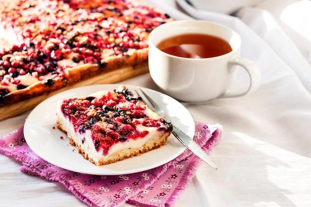 Lekker ontbijt heerlijke taart met diverse bessen en kwark en een kopje thee copy space