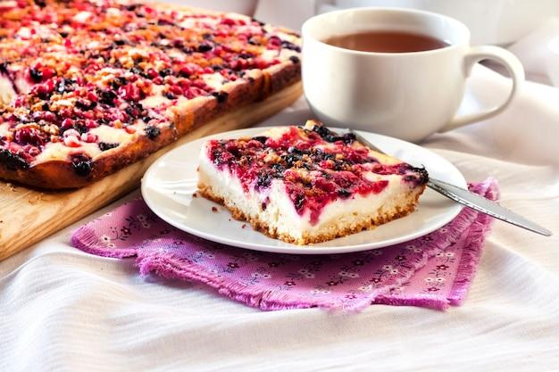 Lekker ontbijt. heerlijke taart met diverse bessen en kwark en een kopje thee Premium Foto