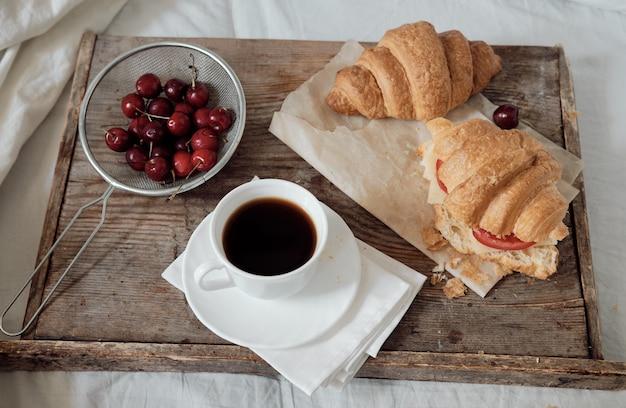 Lekker ontbijt met verse croissants, koffie, kersen op een houten dienblad. hartige croissant met tomaat en kaas. espresso op een ontbijtblad