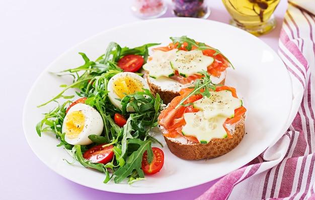 Lekker ontbijt. open sandwiches met zalm, roomkaas en roggebrood in een witte plaat en salade met tomaat, ei en rucola.