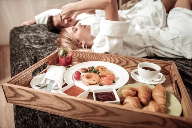 Lekker ontbijt. sluit omhoog van lekker ontbijt met koffie en croissants die zich op bed dichtbij paar bevinden