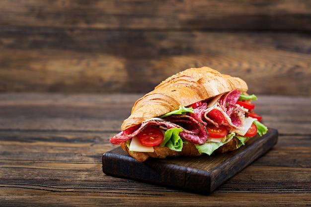 Lekker ontbijt. smakelijke croissant met salami en kaas en tomaten