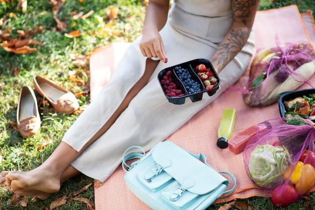 Lekker picknicken. bovenaanzicht van vrouw met getatoeëerde arm genieten van gezonde picknick op mooie warme dag