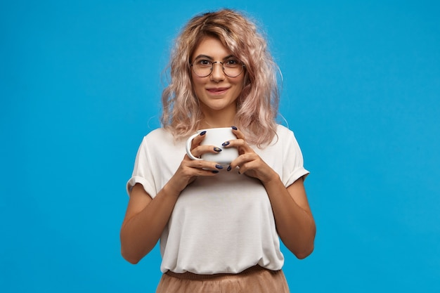 Lekker. portret van leuk nerdy jong wijfje die ronde oogglazen dragen die van zoete hete chocolademelk genieten. mooi meisje met roze haar met witte mok, goede verse koffie drinken