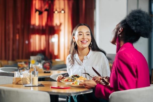 Lekker samen lunchen twee collega's die zich uitgerust voelen terwijl ze samen lekker lunchen in de pauze
