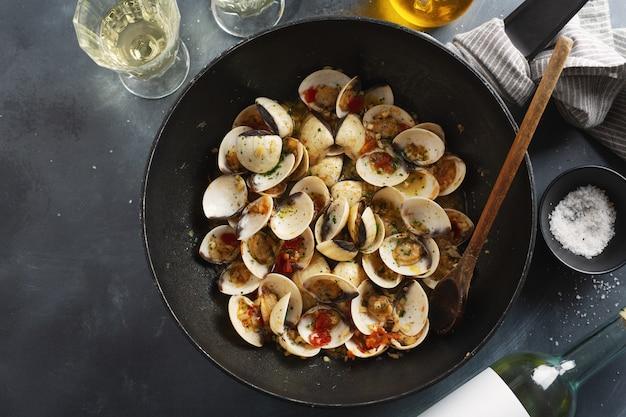 Lekker smakelijke verse zelfgemaakte mosselen alle vongole met knoflook en witte wijn op pan. bovenaanzicht.