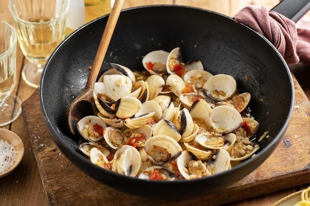 Lekker smakelijke verse zelfgemaakte mosselen alle vongole met knoflook en witte wijn op pan. detailopname.