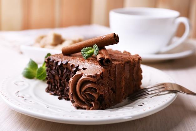 Lekker stukje chocoladetaart met munt en kaneel op houten tafel en wazig planken