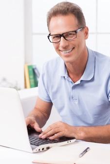 Lekker thuis werken. zelfverzekerde volwassen man die op laptop werkt en glimlacht terwijl hij thuis op de bank zit