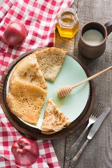 Lekker traditioneel russisch ontbijt van pannenkoeken met honing op plaat. rustieke stijl.
