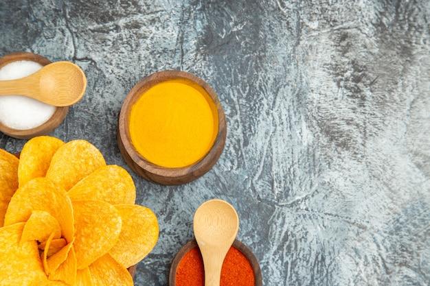 Lekkere aardappelchips versierd als bloemvormige verschillende kruiden met lepels erop op grijze tafel