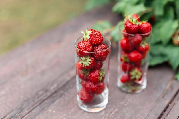 Lekkere aardbeien in een glas op een houten tafel in de tuin