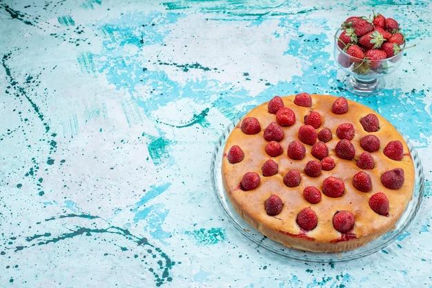 Lekkere aardbeientaart met fruit en samen met verse rode aardbeien op helderblauw bureau, cakedeeg koekje fruitbes