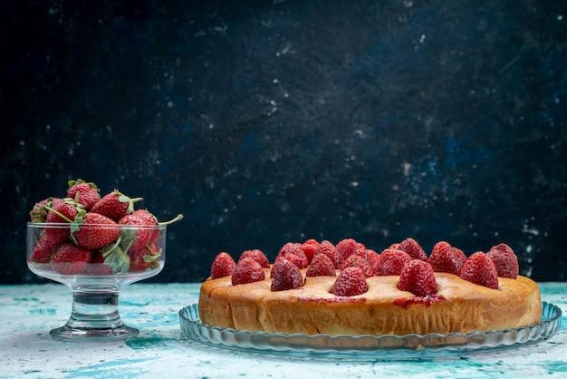 Lekkere aardbeientaart rond gevormd met fruit en samen met verse rode aardbeien op helderblauw bureau, cakedeeg koekje fruitbes