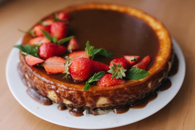 Lekkere aardbeientaart versierd met muntblaadjes op houten tafel. karamelglazuur bovenop taart.