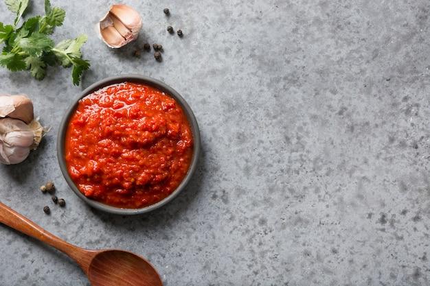 Lekkere ajvar. groentesaus of kaviaar van gebakken rode paprika op grijs. balkan-keuken.