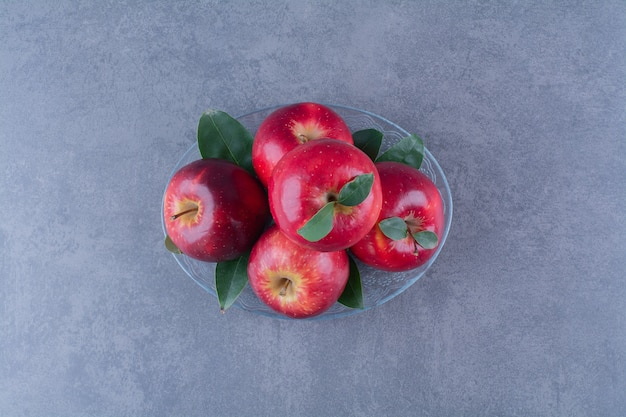Lekkere appels op een glasplaat op marmeren tafel.