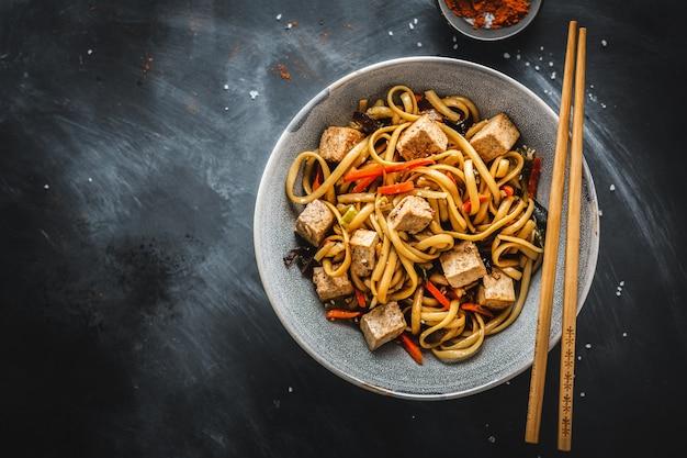 Lekkere aziatische noedels met kaas tofu en groenten in kommen