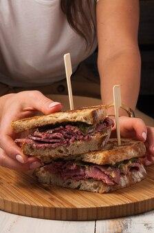 Lekkere beef sandwich in de hand van het meisje.