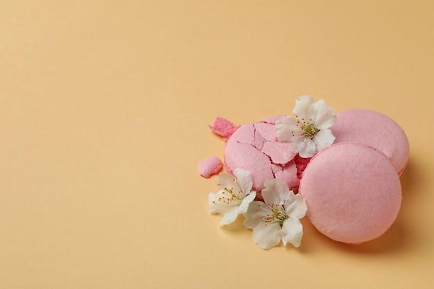 Lekkere bitterkoekjes en bloemen op beige achtergrond
