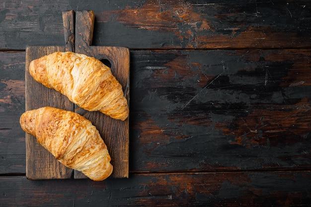 Lekkere boterachtige croissants set, op oude donkere houten tafel achtergrond, bovenaanzicht plat lag, met kopie ruimte voor tekst