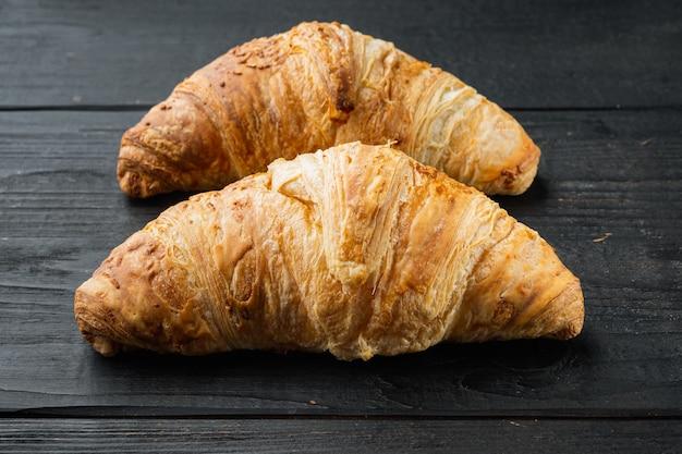 Lekkere boterachtige croissants set, op zwarte houten tafel achtergrond