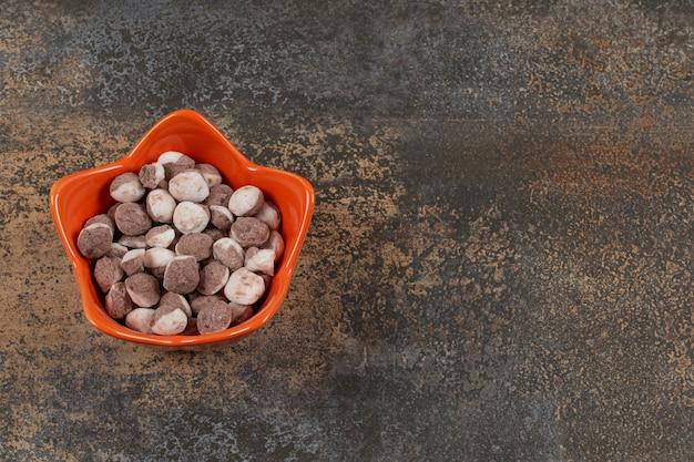 Lekkere bruine snoepjes in oranje kom.