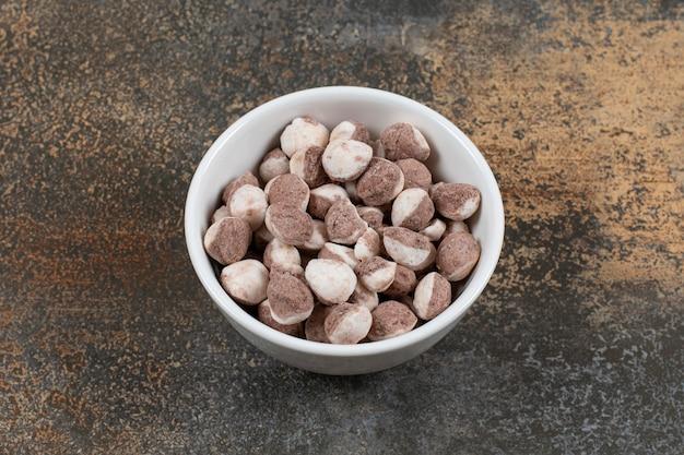 Lekkere bruine snoepjes in witte kom.