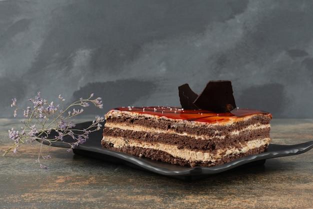Lekkere cake op plaat met bloem op marmeren oppervlak.