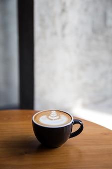Lekkere cappuccino met mooie latte kunst op houten tafel in het café.