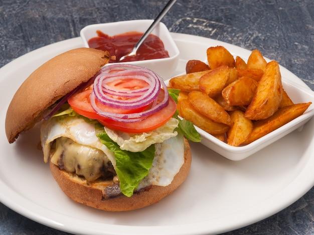 Lekkere cheeseburger met aardappelschijfjes en tomatensaus