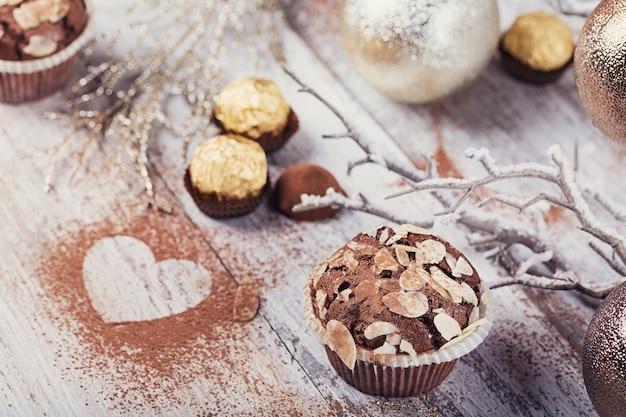 Lekkere chocolade cupcake met snoep, hartvormige cacaopoeder en winterdecoratie op witte rustieke houten tafel. winter vakantie achtergrond.