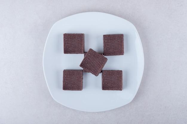 Lekkere chocolade gecoate wafeltjes op een bord op marmeren tafel.