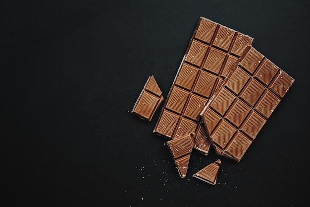 Lekkere chocoladerepen op donkere achtergrond. uitzicht van boven. chocolade achtergrond.