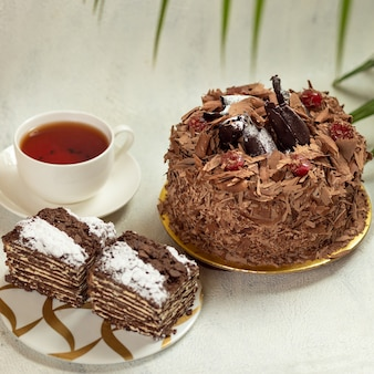 Lekkere chocoladetaart met kopje thee op wit wordt geïsoleerd