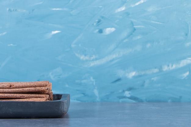 Lekkere chocoladewafelrol in een houten bord op het marmeren oppervlak