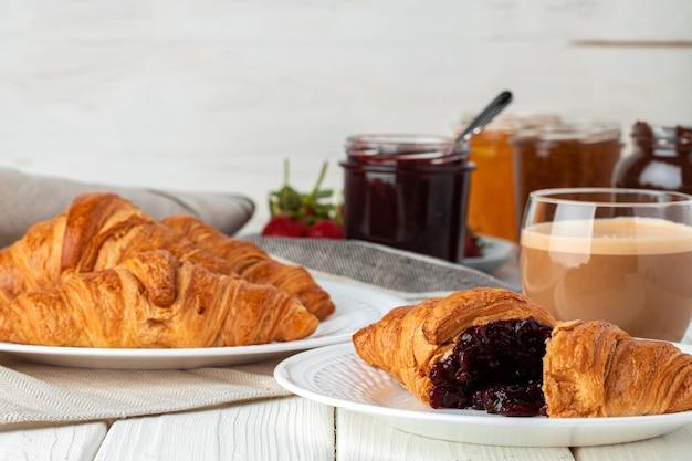 Lekkere croissant met kopje koffie met melk op keukentafel